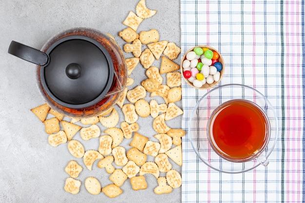 Theepot en een kopje thee op een handdoek met verspreide koekjeschips en een kom snoep op een marmeren oppervlak.