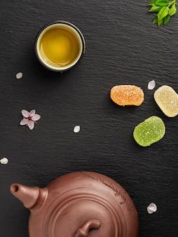 Theepot en kleine kopjes met groene thee staan op een zwarte stenen tafel naast snoep