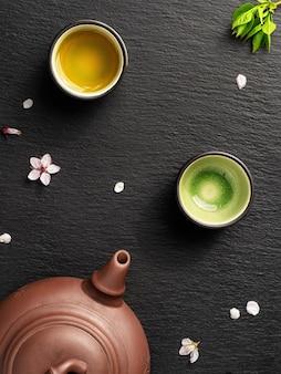 Theepot en kleine kopjes met groene thee staan op een zwarte stenen tafel