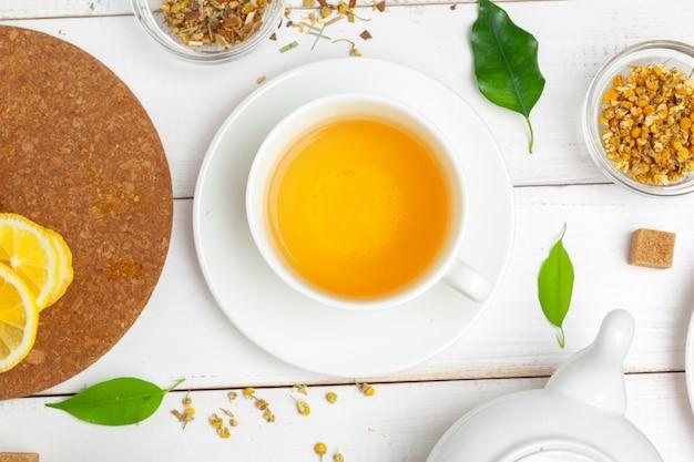Theepot en kop theeën op witte houten