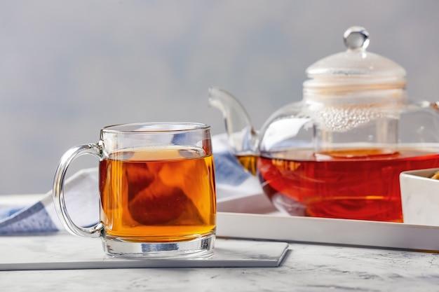 Theepot en kop warme drank op tafel