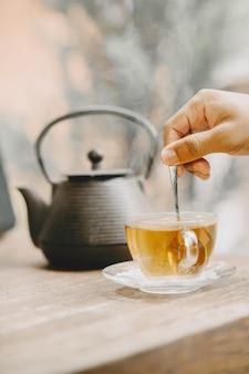 Theepot en kopje hete thee op een tafel. hand met een theelepel