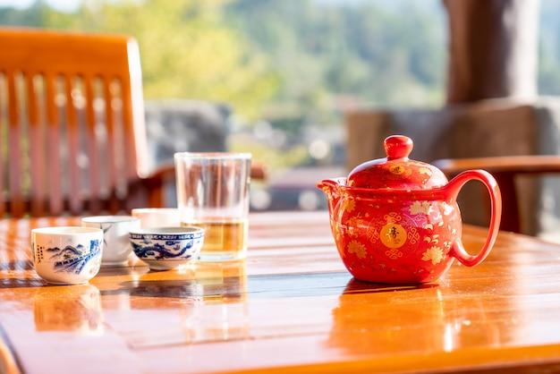 Theepot en kopje op de tafel met ochtendzon