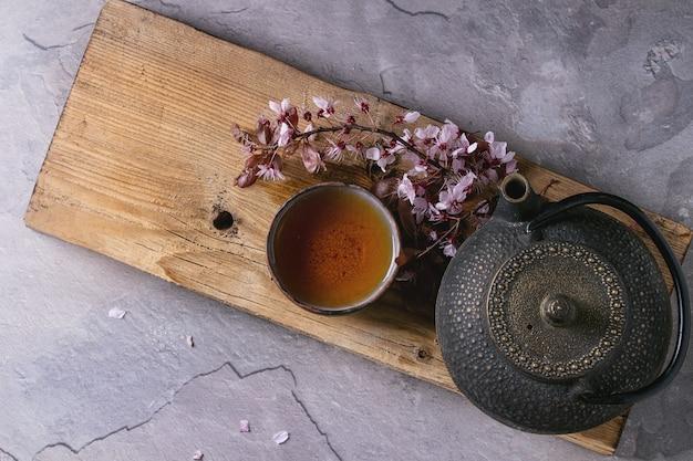 Theepot en kopje thee met bloesem tak