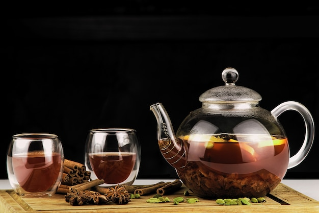 Theepot en kopje thee op een donkere achtergrond