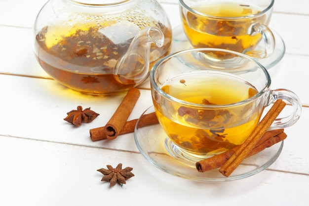 Theepot en kopjes thee op een witte houten achtergrond