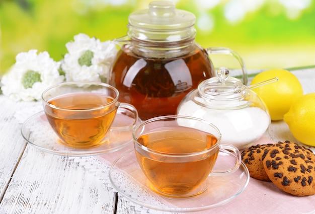 Theepot en kopjes thee op tafel op een helder oppervlak