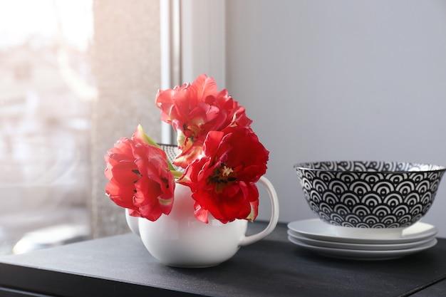 Theepot met mooie bloemen en servies op tafel bij het raam