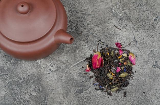 Theepot met thee en een stapel geurende losse theebladeren en knoppen van droge bloemen