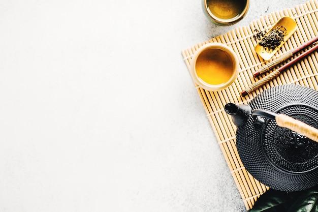 Theepot met thee op lichte achtergrond