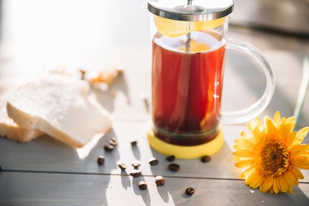 Theepot met toast en bloem op tafel