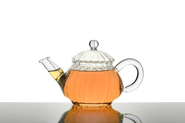 Theepot met wat thee binnen op een witte achtergrond