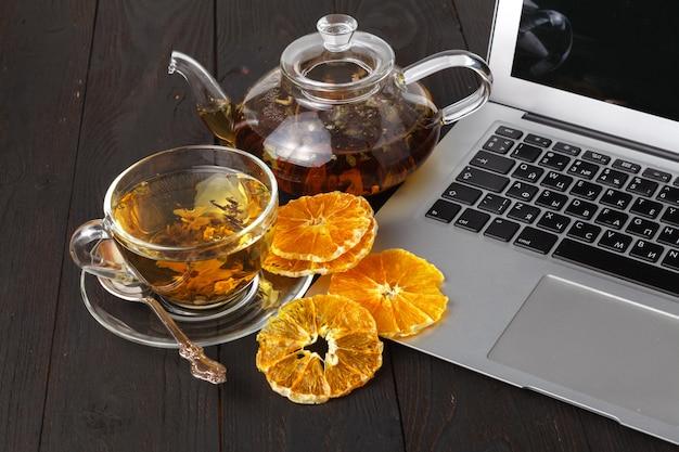 Theepot met zwarte thee, rozen, sinaasappels en grapefruit op hout