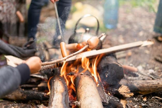 Theepot sauasge gegrild kampvuur op natuur picknick vreugdevuur voedsel bereiden bos wandelen