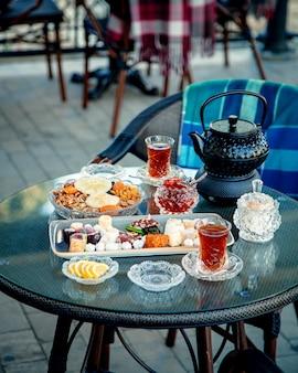 Theeservies met veel snoep en zwarte thee