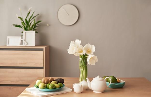 Theeservies op houten tafel. home interieur, boeket bloemen in vaas, tafel met set van theepot. goedemorgen concept. engels ontbijt. ontbijt op hotelkamer
