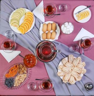 Theetafel met thee en verschillende zoetigheden en snacks.
