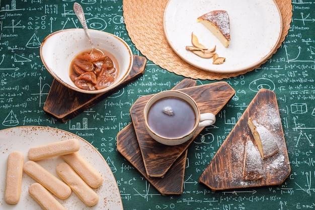 Theetijd, abrikozenjam, kwarktaart en kopje thee op houten planken, wiskundige formules op tafelkleedachtergrond.