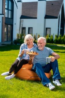 Theetijd. bejaarde vrouw en man die zich ontspannen voelen met theetijd en wat koekjes eten buiten het zomerhuis