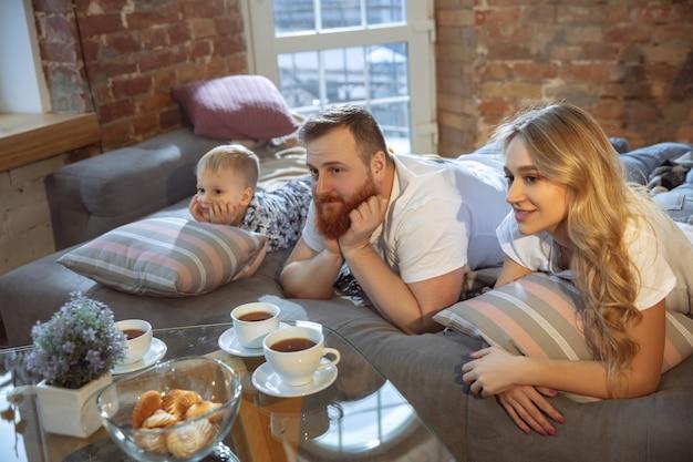 Theetijd. moeder, vader en zoon hebben thuis plezier, comfort en gezellig, liefdesconcept. ziet er vrolijk, vrolijk en vrolijk uit. mooie kaukasische familie. tijd samen doorbrengen, spelen, film kijken.