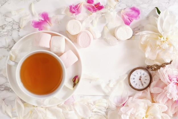 Theetijd. plat leggen met pioenen, marshmalows en een kopje thee
