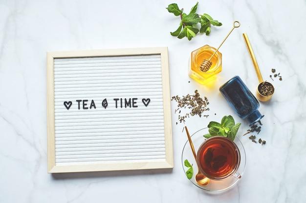 Theetijd wit letterbord met tekst op marmeren tafel met glazen kopje thee met muntblaadjes