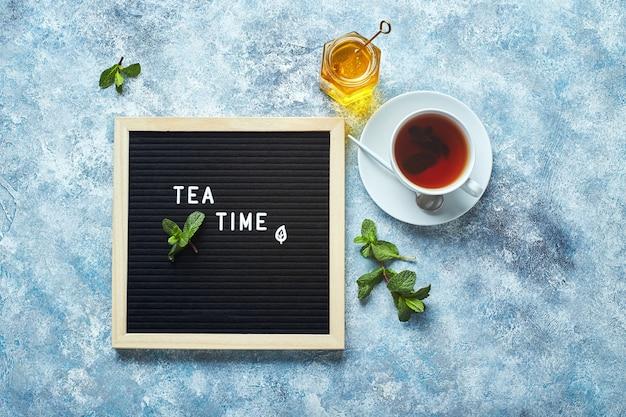 Theetijd zwarte letterbord met tekst op blauwe tafel met glazen kopje thee met muntblaadjes