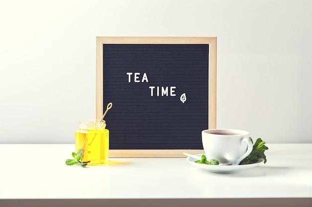 Theetijd zwarte letterbord met tekst op tafel met glazen kopje thee met muntblaadjes