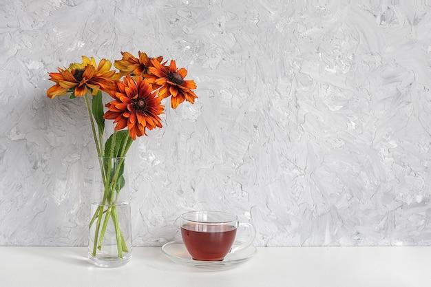 Theetijd. zwarte thee in transparante kop met schotel en boeket van oranje bloemen coneflowers in vaas op tafel