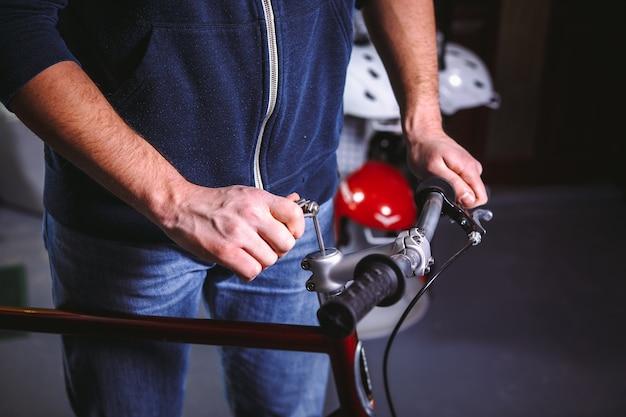 Thema reparatiefietsen. close-up van de hand van een blanke gebruik een handgereedschap inbussleutel om de stelen te installeren een fietsstuurbevestiging voor een racefiets