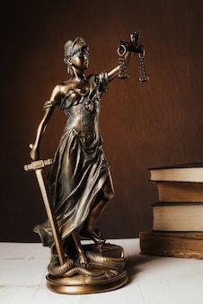 Themis beeldje staat op een witte houten tafel naast een stapel oude boeken. schalen wet advocaat bedrijfsconcept. - afbeelding