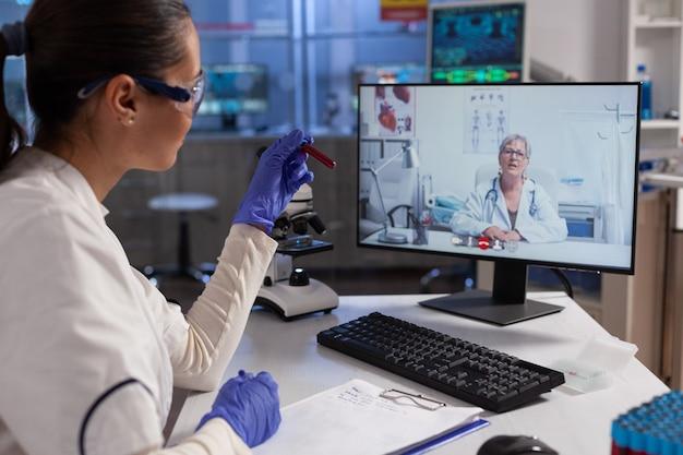 Therapeut arts die reageerbuisjes vasthoudt en bloedexpertise bespreekt met chemicus op afstand