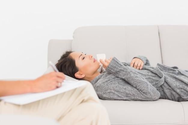 Therapeut die aantekeningen maakt over haar huilende patiënt op de bank