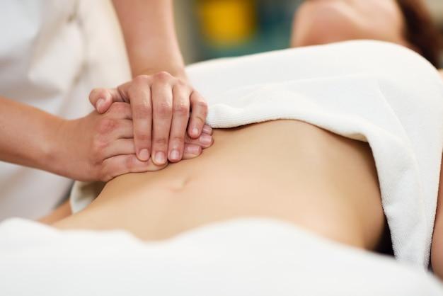 Therapeut die druk op buik uitoefent. handen die vrouwenbuik masseren.