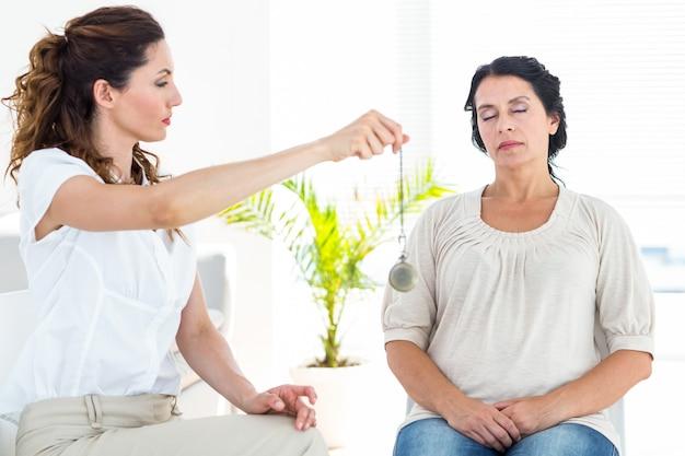 Therapeut die haar patiënt hypnotiseert