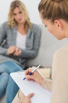 Therapeut die nota's op haar klembord schrijft