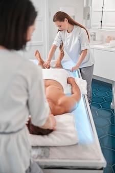 Therapeut gebruikt hulpmiddel om het been van de man te masseren die werkt met een bekwame collega in het ziekenhuiskantoor