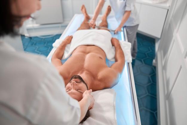 Therapeut masseert hoofd van man terwijl jonge collega met zijn benen in het ziekenhuis werkt