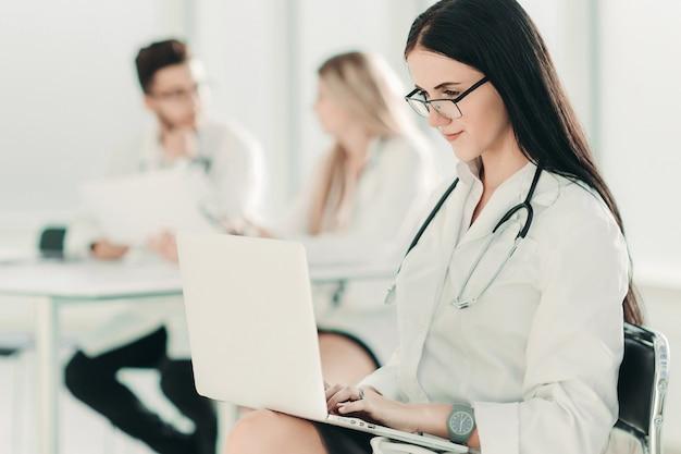 Therapeut met een laptop zittend in het ziekenhuiskantoor