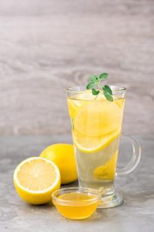 Therapeutische drank van citroen, honing en munt in een glas op tafel. alternatieve geneeskunde, behandeling met folkremedies.