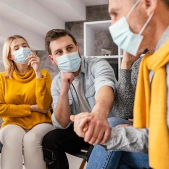 Therapie gemeenschap met chirurgische masker hand in hand