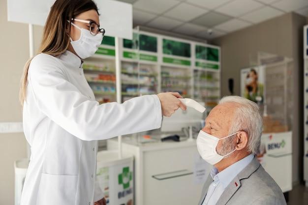 Therapie in een verpleeghuisapotheek op het moment van coronavirus. een jonge apotheker meet de temperatuur van een volwassen man