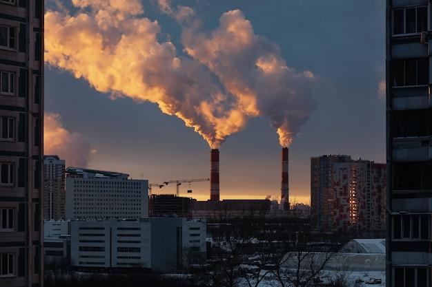 Thermische centrale met rookpijpen, bouwkranen, industriële installaties en woongebouwen. milieuvervuiling. avond, zonsondergang.