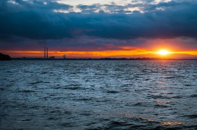 Thermische elektriciteitscentrale in de verte in de zee met zonsondergang bewolkte hemel