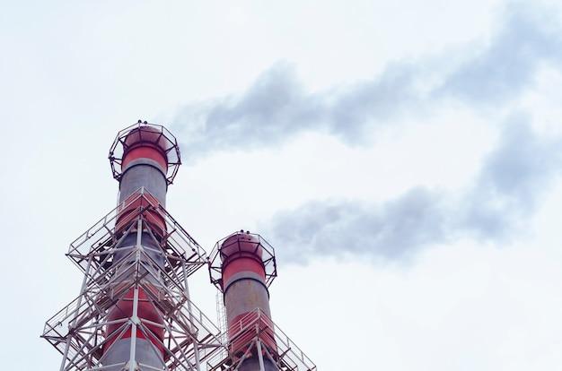 Thermische energiecentrale, de uitstoot van stoom en rook in de atmosfeer door een industriële pijp, milieuvervuiling.