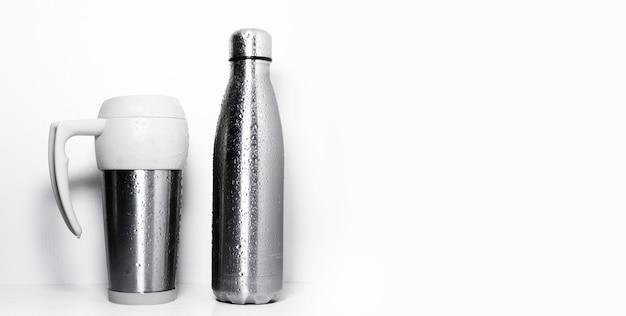 Thermo mok en herbruikbare stalen fles, bespoten met water, geïsoleerd op een witte achtergrond met kopie ruimte.
