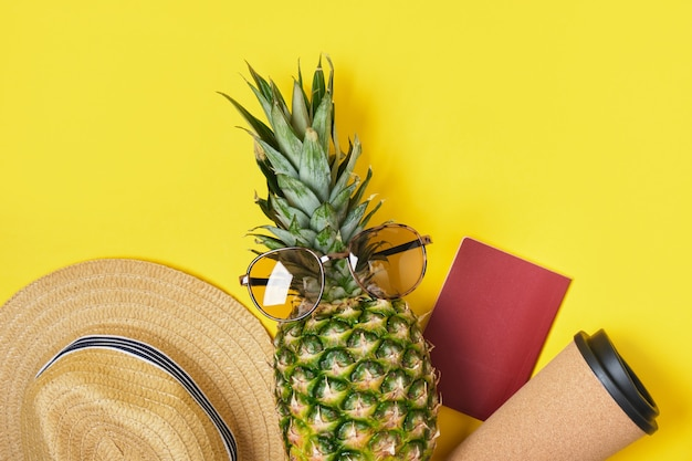 Thermobeker, ananas, strohoed, zonnebril en blanco paspoort op gele achtergrond
