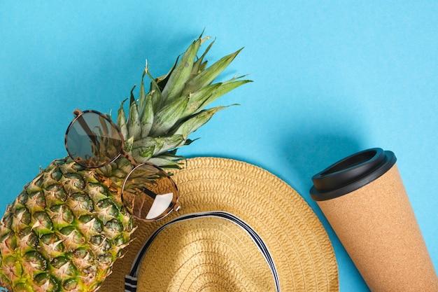 Thermokop, ananas in zonnebril en strohoed op blauwe achtergrond