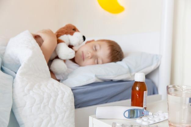Thermometer, medicijnen en een glas water op de tafel bij de zieke slapende peuter bo