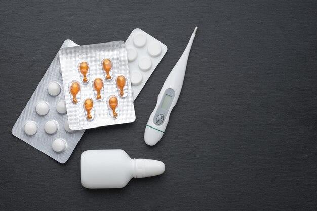 Thermometer, neusdruppels en tabletten op donkere leisteen bord. plat liggen. medicijnen voor schoorsteenbehandeling, gezondheidszorgconcept.